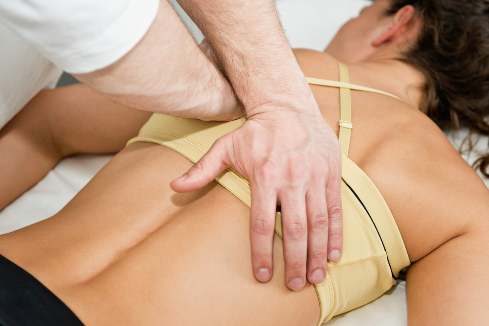 Chiropractor adjusting patients back
